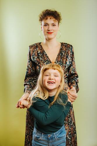 Porträt einer alleinerziehenden Mutter und ihrer vorpubertären Tochter vor grünem Hintergrund Erwachsener Pflege Kaukasier heiter Kind Kindheit niedlich Emotion