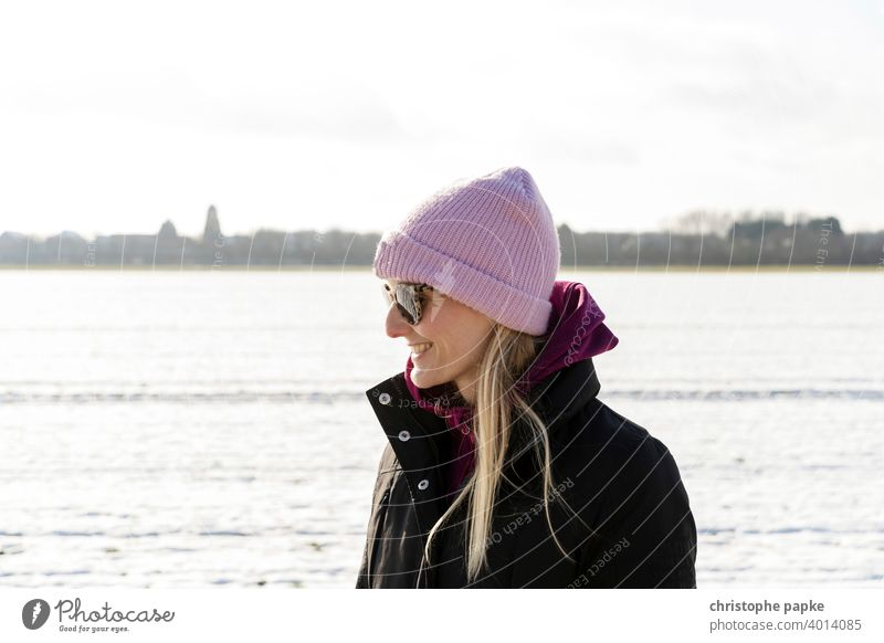 Frau mit Mütze in verschneiter Landschaft kalt Winter Lächeln blond Sonnenbrille hell Porträt Junge Frau Außenaufnahme Schnee Natur Farbfoto Mensch Lifestyle