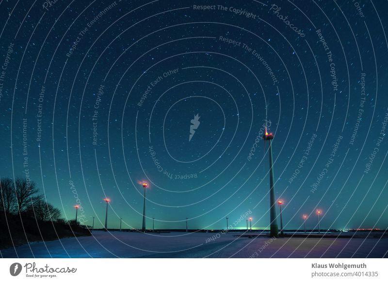 Winternacht mit Sternenhimmel über Windrädern auf einem schneebedeckten Feld Nacht Sterenhimmel Großer Wagen Schnee Frost Langzeitbelichtung Ebene