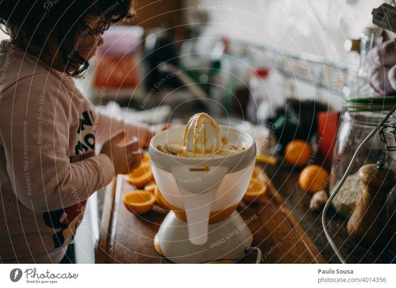 Kind macht Orangensaft zu Hause orange frisch Kindheit Vorbereitung Vitamin Vitamin C saftig Zitrusfrüchte Gesunde Ernährung Bioprodukte Nahaufnahme lecker