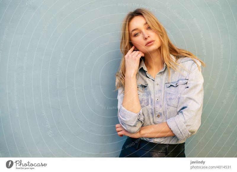 Blonde Frau in Jeanshemd und schwarzem Lederrock steht auf der Straße. Mädchen blond Russisch blau Auge Porträt Mode im Freien Dame Frisur Person weiß hübsch