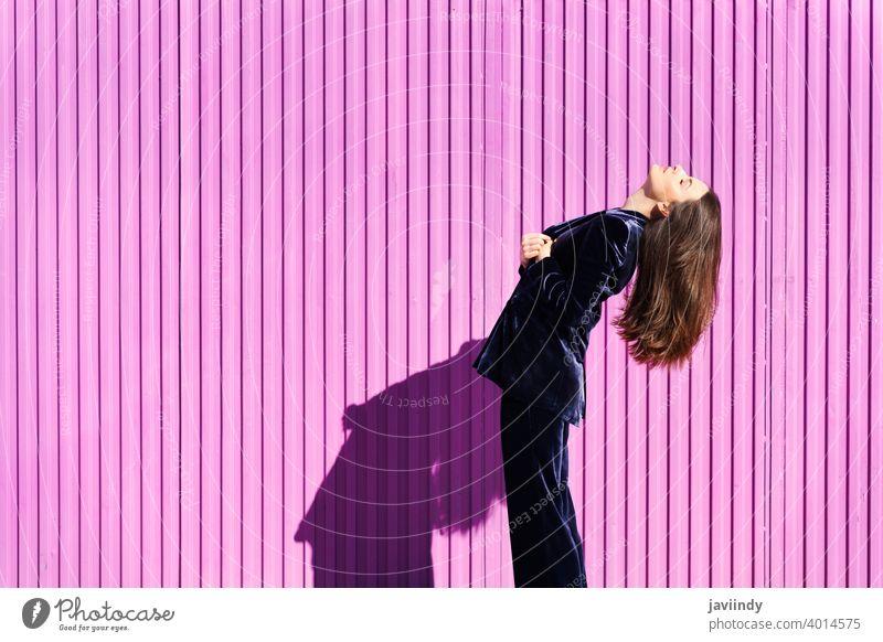 Frau in blauem Anzug posiert in der Nähe eines rosa Rollladens. Frisur Behaarung Mode Model Gebäude blind Fuchsie purpur bewegend Mädchen Person Lifestyle urban