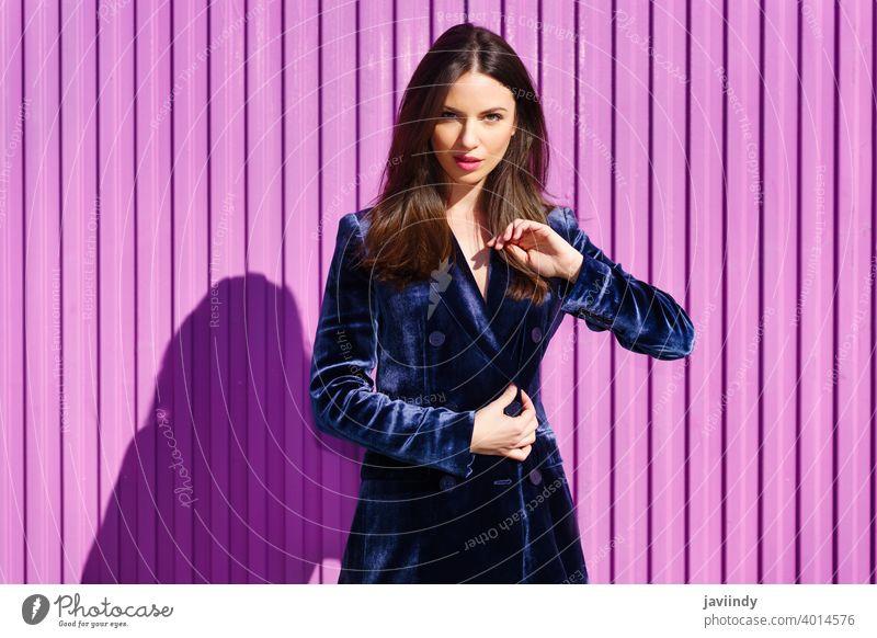 Frau in blauem Anzug posiert in der Nähe eines rosa Rollladens. Mädchen Person Mode Model Lifestyle urban Hintergrund Dame elegant Gebäude blind außerhalb