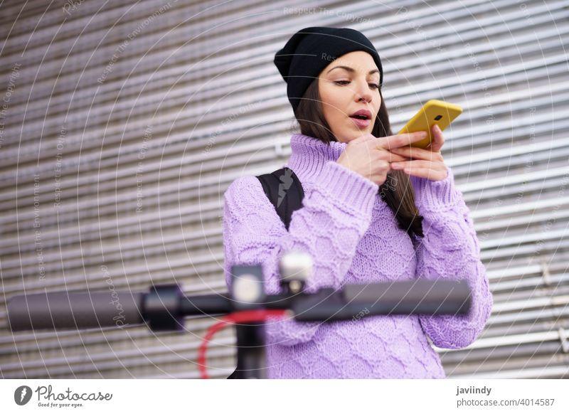 Frau in den Zwanzigern mit Elektroroller nimmt im Freien eine Sprachnotiz mit einem Smartphone auf. Stimme Hinweis klug Telefon Tretroller elektrisch E-Roller