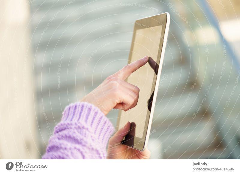 Detail einer nicht erkennbaren Frau, die im Freien ein digitales Tablet benutzt. Tablette Gerät unkenntlich Schüler Mädchen Winter Verschlussdeckel Rucksack