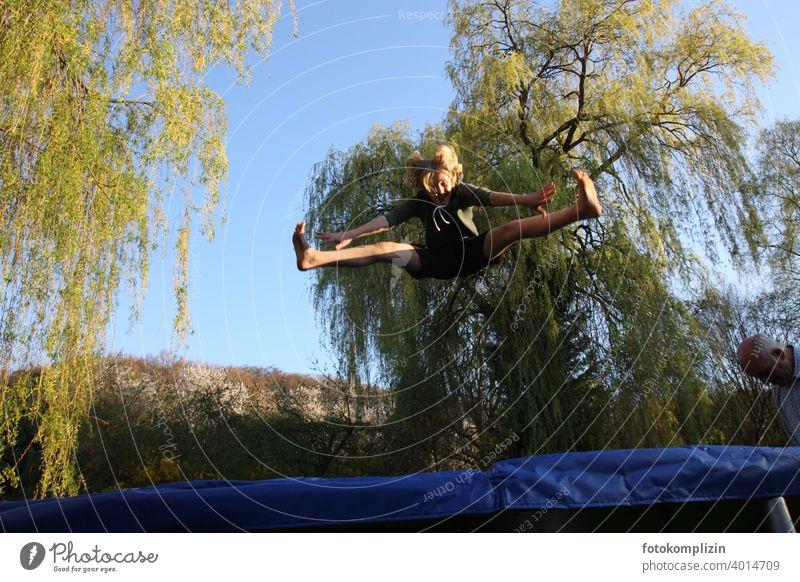 Teenager springt auf einem Trampolin hüpfen Sprung Sprungkraft turnen akrobatisch springen Fitness Freude beweglich Jugendliche Bewegung Lebensfreude Sport