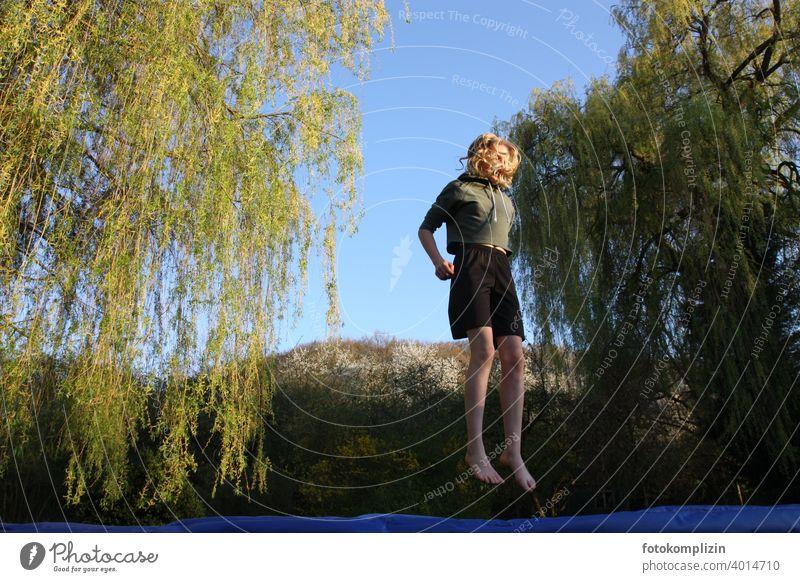 Teenager hüpft auf einem Trampolin hüpfen springen beweglich Lebensfreude Bewegung Jugendliche Körperbeherrschung Aktion aktivität sich spüren lebendig