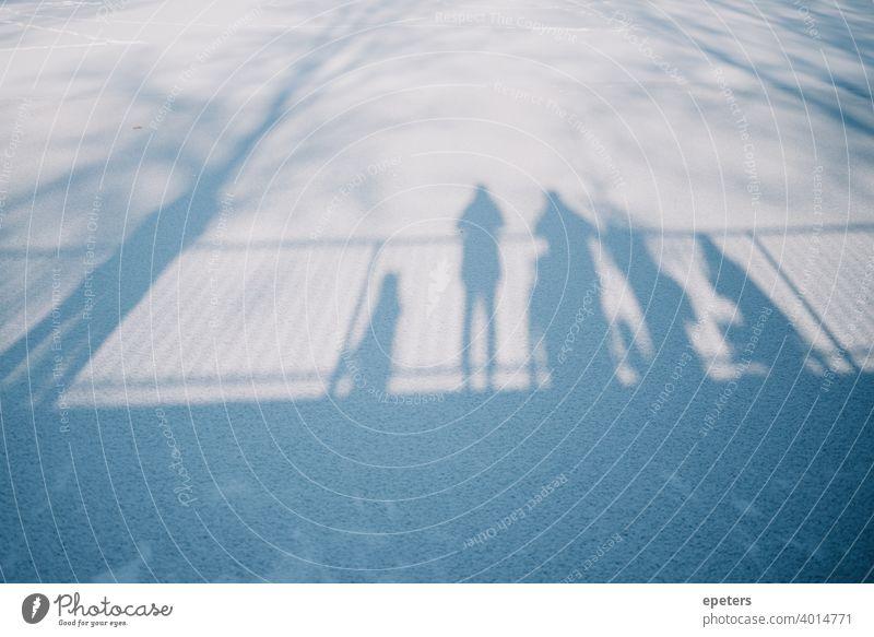 Schatten mehrerer Menschen die auf einer Brücke stehen und auf einen zugefrorenen See schauen Steilshoop blau schatten Außenaufnahme Farbfoto Stadt Tag trist