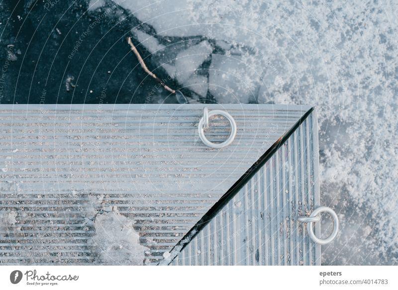 Kante eines Stegs über gefrorenem Wasser an einem See grau ultimatives Grau blau Eis Schnee Winter kalt Ring Ringe Scheidung Kälte weiß hell Eisscholle