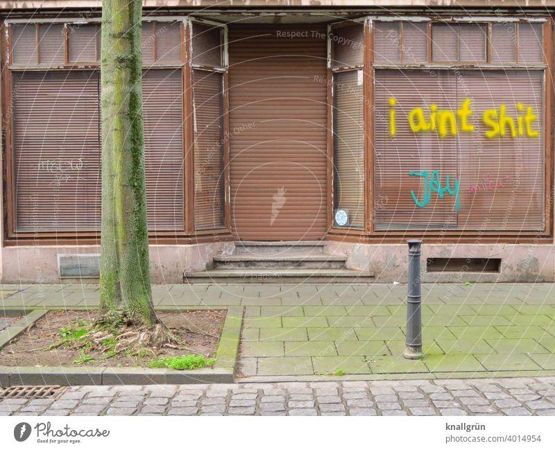 I aint shit Haus Graffiti Architektur Gebäude Fassade Außenaufnahme Stadt Menschenleer Tag Rolladen geschlossen verfallen alt Fenster Gedeckte Farben Verfall