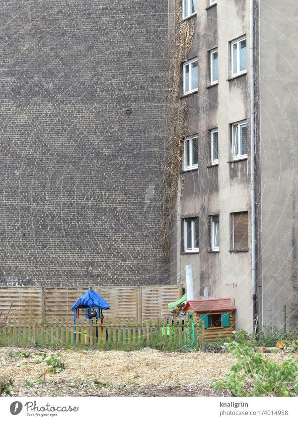 Spielplatz im Hinterhof Tristesse Kindheit Spielen Außenaufnahme Menschenleer Farbfoto Einsamkeit trist Zentralperspektive öde Traurigkeit Haus Zaun