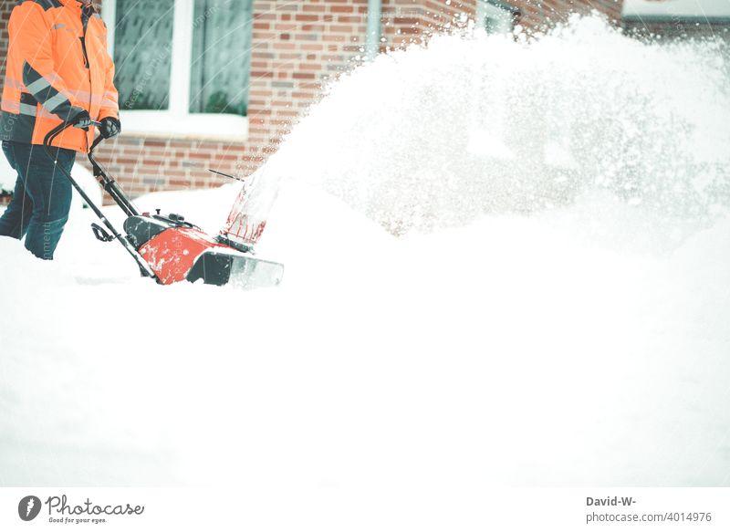 Mann räumt im Winter mit einer Schneefräse den Schnee beiseite schneefräse Schneemassen viel Winterdienst Unwetterwarnung Wetter Wintereinbruch Weg Schneefall