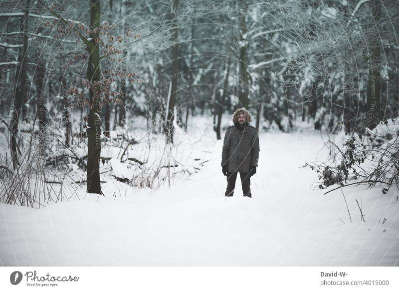 Mann steht bei eisiger Kälte in einem verschneiten Wald winter kalt Schnee kühl kälte Winterstimmung Wintertag wandern winterlich Winterwald frieren Dezember