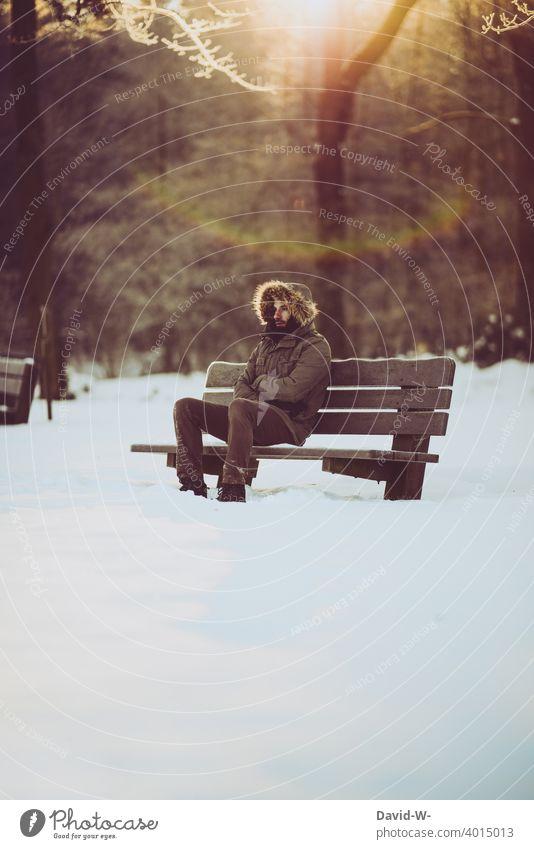 Mann sitzt frierend bei eisiger Kälte auf einer Bank in der Natur Winter kalt Schnee weiß Wintertag Winterstimmung sitzen Wintereinbruch Sonnenlicht