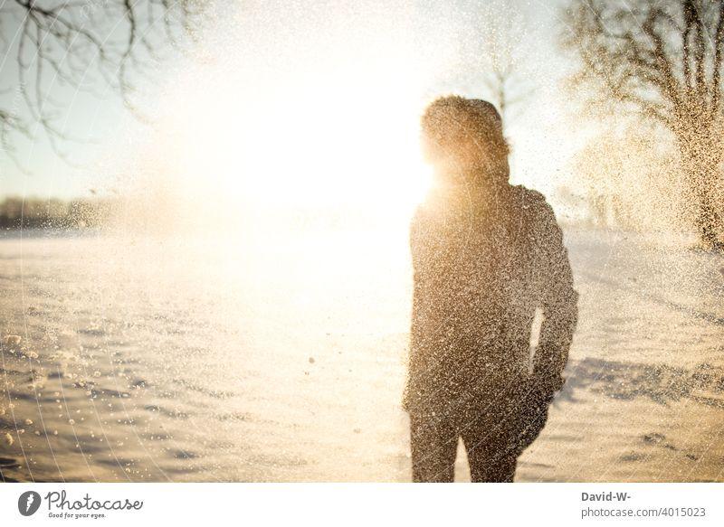 Mann im Schnee im Licht der Sonne Winter Sonnenstrahlen Wintermorgen Winterstimmung kalt Schönheit Natur Wintereinbruch Schneefall Wintertag Landschaft weiß