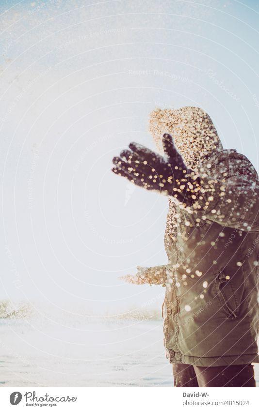 Mann steht im Schneegestöber Schneefall Schneeflocken Freude Winter Wintertag Wintereinbruch winterlich Sonnenlicht Winterstimmung Wetter kalt