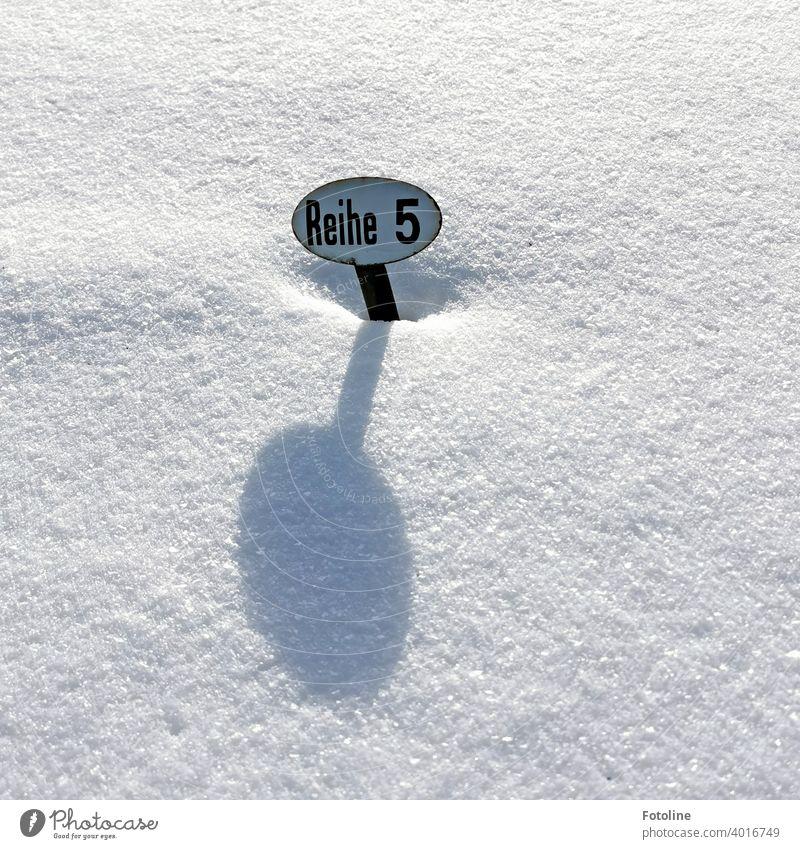 Reihe 5 steht auf einem kleinen Blechschild auf einem Friedhof, völlig eingeschneit. Schild Schilder & Markierungen Hinweisschild Außenaufnahme Menschenleer
