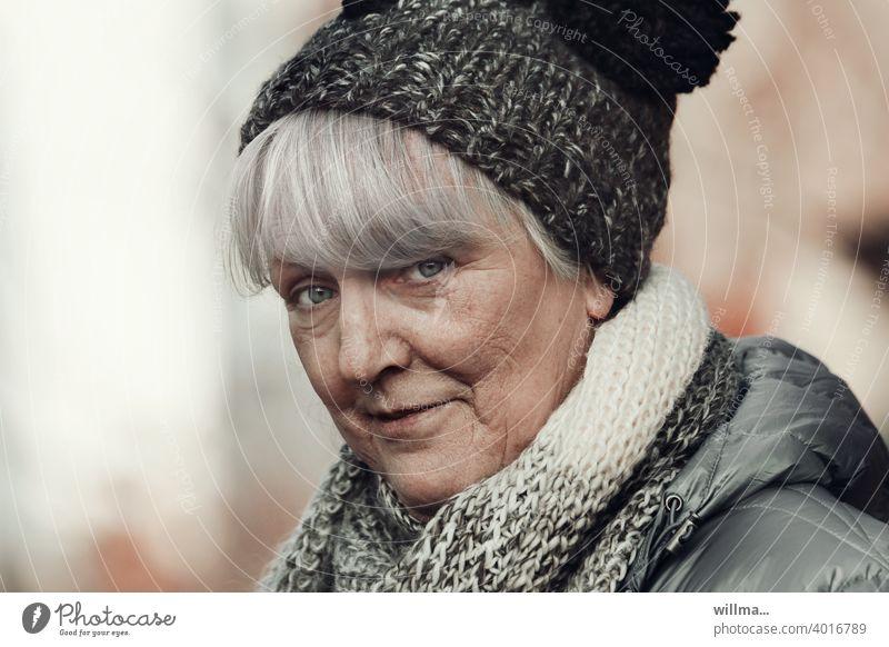 verschmitzte Seniorin mit Bommelmütze Porträt weißhaarig Schal Blick in die Kamera Skeptischer Blick Skepsis Pony fragend Wollmütze