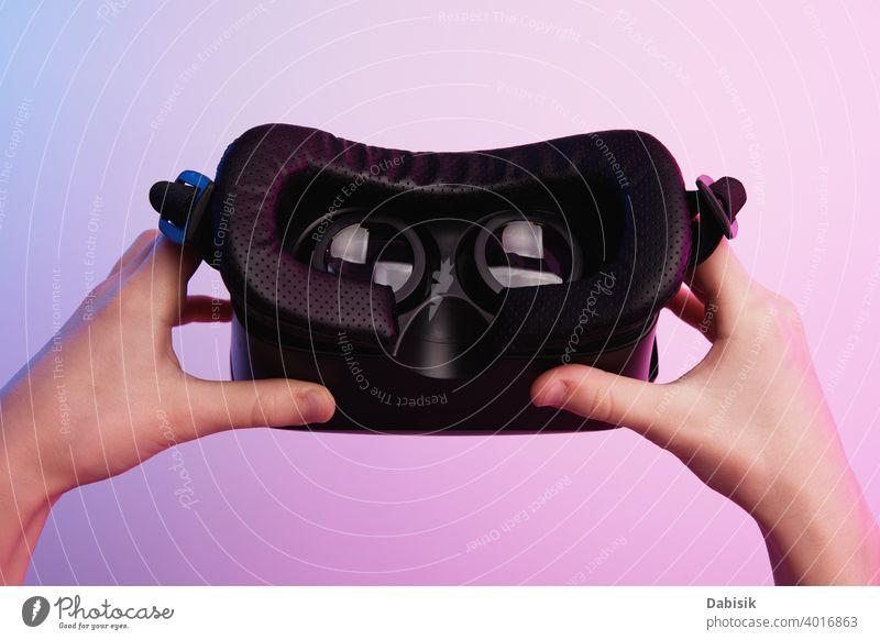 Virtual-Reality-Brille in der Hand auf buntem Hintergrund. Zukunftstechnologie, VR-Konzept Headset virtuell Realität weiß Schutzhelm Technik & Technologie Gerät