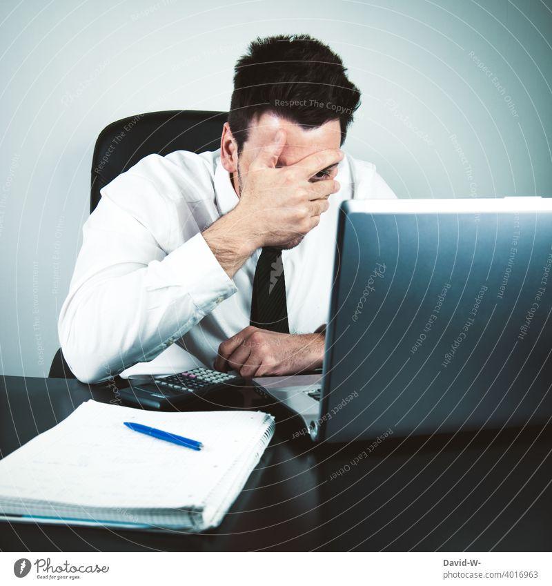 ängstlicher Geschäftsmann vor dem Laptop hält seine Hand vor das Gesicht Mann Notebook Misserfolg geschockt angst Business Homeoffice Schreibtisch arbeiten Büro