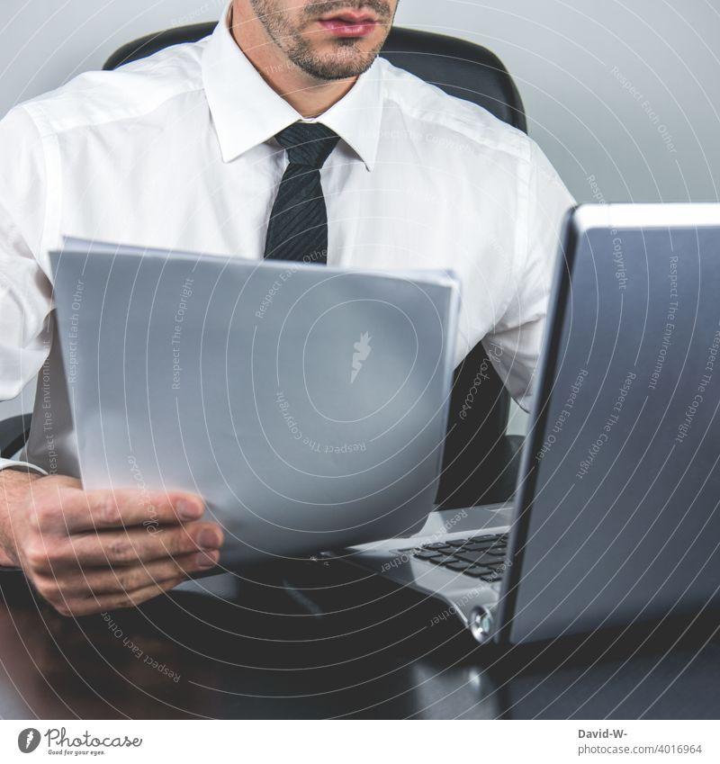 Mann arbeitet am Laptop und hält Unterlagen in der Hand Homeoffice Compter arbeiten Rechnungen Notebook Arbeitsplatz Büro online Anzug