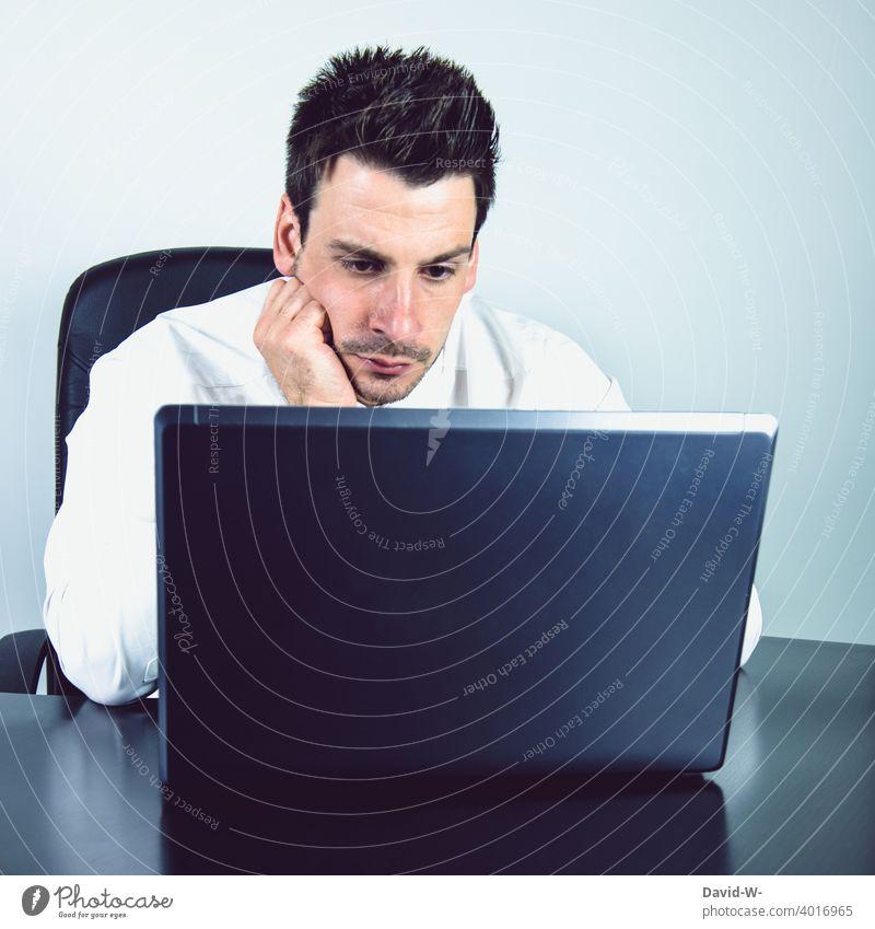 Mann am Laptop Homeoffice ernst konzentriert Computer arbeit online Arbeit arbeiten Arbeitsplatz