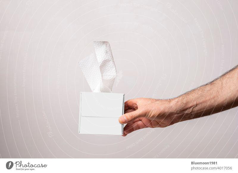 Männliche Hand hält eine kubische Tissue-Box auf weißem Hintergrund Attrappe editierbar Wandel & Veränderung Papier vereinzelt Serviette Vorlage