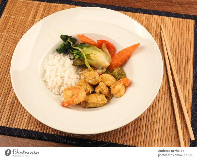 Rotes Thai-Curry mit Huhn und Garnelen mit gebratenem Gemüse und Reis Würzig Hähnchen Chili geschmackvoll Essen zubereiten Küche Gesundheit Salatbeilage hölzern