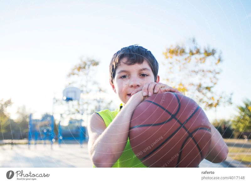 Porträt eines jungen männlichen Teenagers mit ärmellosen stehend auf einer Straße Korbplatz beim Lächeln in die Kamera Basketball Gericht Spieler wirklich