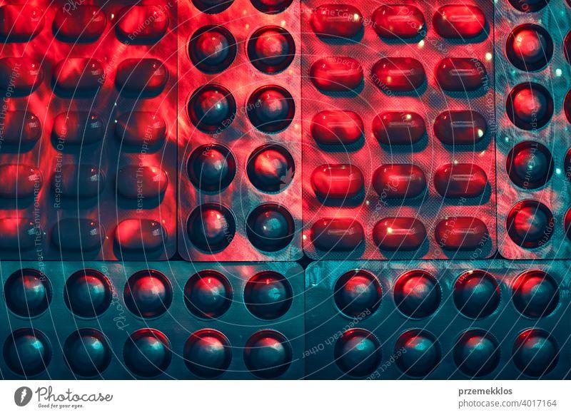 Tabletten und Kapseln Pille in Blisterverpackung in Reihe angeordnet. Medikamente - Tabletten, Pillen in Blisterpackung, Medikamente Medikamente Medikamente in warmem roten und kaltem blauen Licht