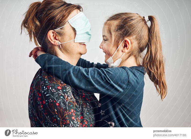 Kleines Mädchen küsst ihre Mutter, die Augen mit Gesichtsmaske zum Spaß bedeckt hat Tochter Kind Familie Frau Küssen Liebe Pflege Kuss Zusammensein Lebensstile