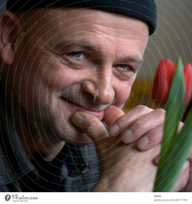 Die Heiterkeit mann mütze blick lächeln tulpe blume gesicht portrait neugierig zufrieden schmunzeln vergnügt vergnüglich heiter heiterkeit