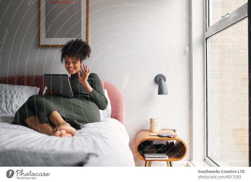 Frau liegend auf Bett zu Hause machen Videoanruf auf digitalen Tablet digitales Tablett Tablet Computer Video-Chat Mitteilung winkend Familie Freunde Sperrung