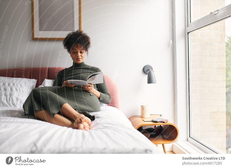 Junge Frau liegend und entspannend auf Bett zu Hause Lesung Buch entspannt lesen studierend Lernen Lehre Selbsthilfe technologiefrei Schlafzimmer Lügen