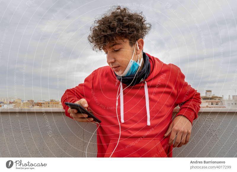 Junger attraktiver Mann mit lockigem Haar und rotem Sweatshirt, der auf der Terrasse des Hauses das Handy benutzt und eine Maske trägt, um sich vor dem Coronavirus zu schützen