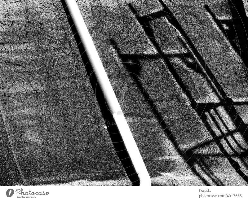 Ein Dach, ein Schatten und Raureif Winter Dachpappe Gerüst Eis kalt Regenrohr