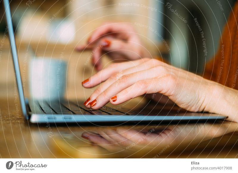 Frauenhäuser tippen zuhause etwas auf der Tastatur eines Laptops Tippen Notebook Homeoffice home Office online arbeiten Hände Computer Arbeitsplatz Internet
