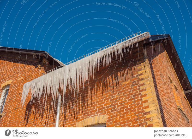 lange Eiszapfen an Dachrinne eines Backsteinhauses im Winter bei eisiger Kälte und Sonne architektur backstein Backsteinhaussiedlung Dachkante dachrinne