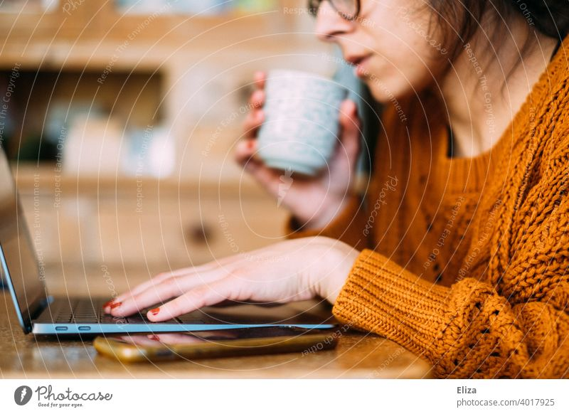 Eine Frau sitzt mit Kaffee und Laptop Zuhause am Tisch und arbeitet im Home Office Homeoffice zuhause arbeiten Kaffeetasse Notebook Computer Arbeitsplatz