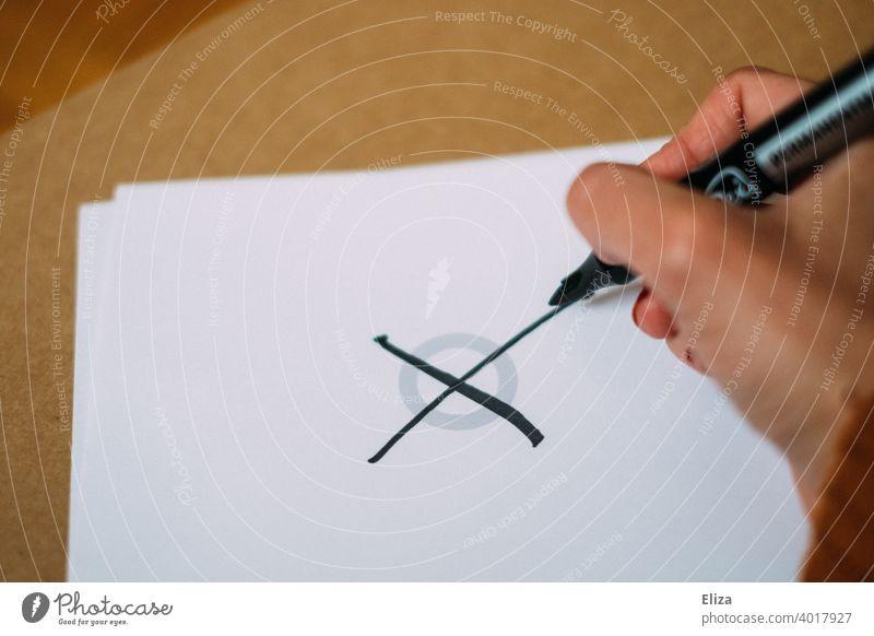 Hand macht ein Kreuz in einem Kreis. Wählen gehen. Bundestagswahl. Kreuz machen Wahl Wahlen Politik & Staat Demokratie Stimmabgabe Entscheidung wählen