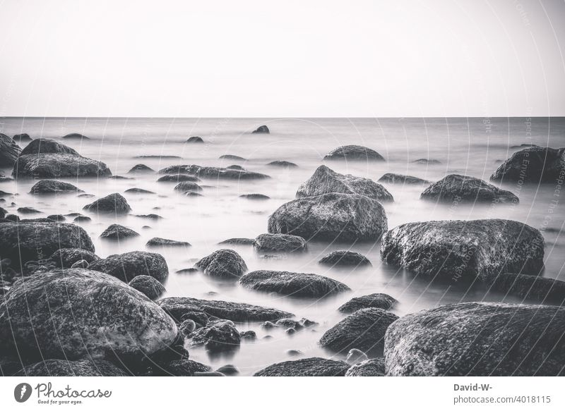 Langzeitbelichtung von Felsen / Steinen im Meer neblig Nebelschleier ruhe Küste Menschenleer milchig Ozean verwunschen verträumt