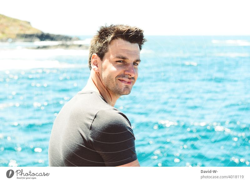 Mann im Urlaub am Meer schaut in die Kamera Ferien & Urlaub & Reisen Urlauber Ozean Blick in die Kamera zufrieden ruhe Meeresrauschen blau Küste