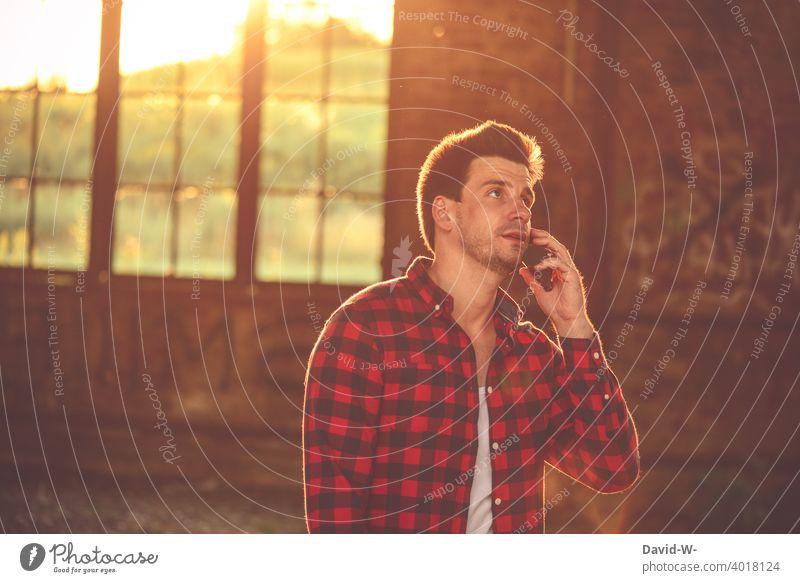 Mann telefoniert mit dem Handy telefonieren Sonnenlicht Sonnenschein Gespräch mobil besprechen Smartphone Lifestyle erreichbar