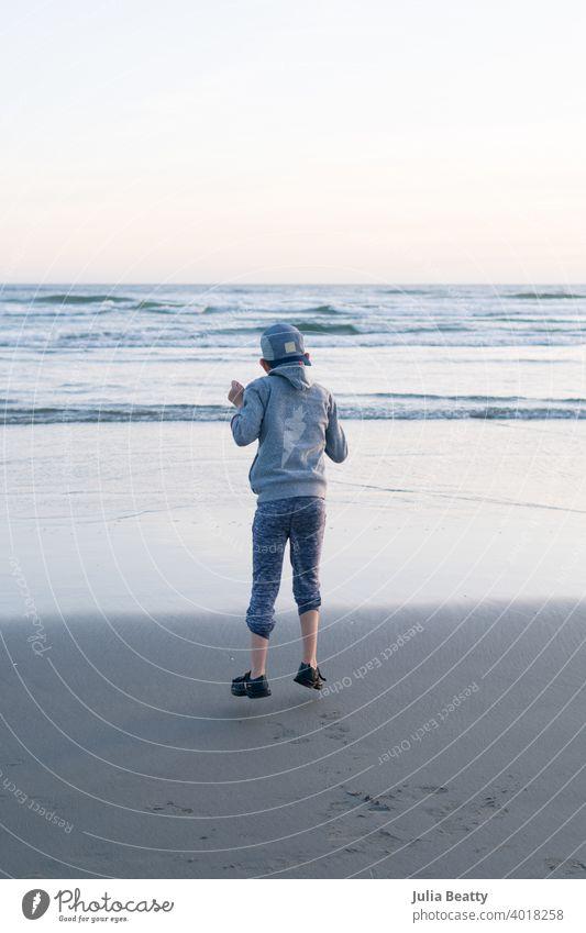 Kind mit Autismus, das vor Freude in die Luft springt; Hintergrund ist ein Strand mit Wellen springen in der Luft Air Stoppbewegung frieren Glück Junge Kindheit