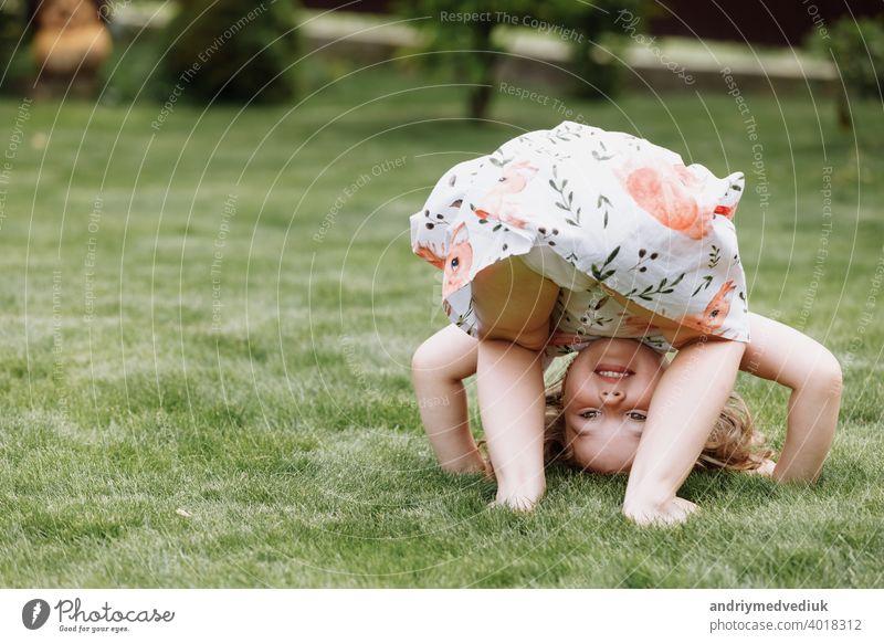 Kleines glückliches Mädchen, das Spaß im grünen Sommerpark hat. glückliche Kindheit schön niedlich Natur Frühling Gras jung Fröhlichkeit Glück Freude wenig