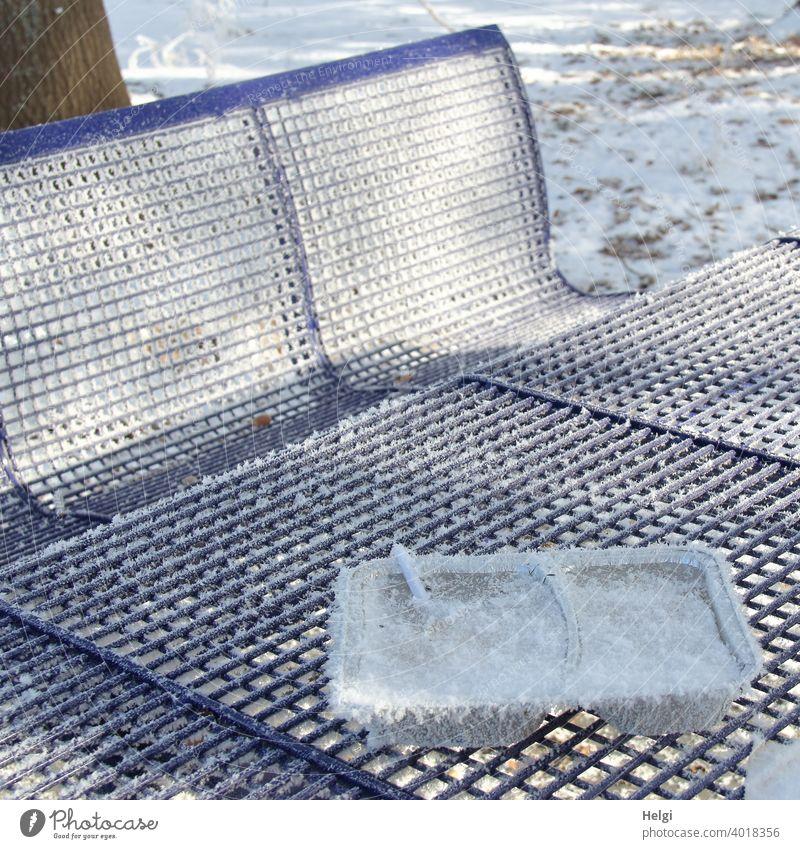 auswärts essen - mit Raureif bedeckte Restverpackung einer Mahlzeit sowie Tisch und Bänke auf einem Rastplatz Müll Restmüll Verpackung Bank Pause Winter Kälte