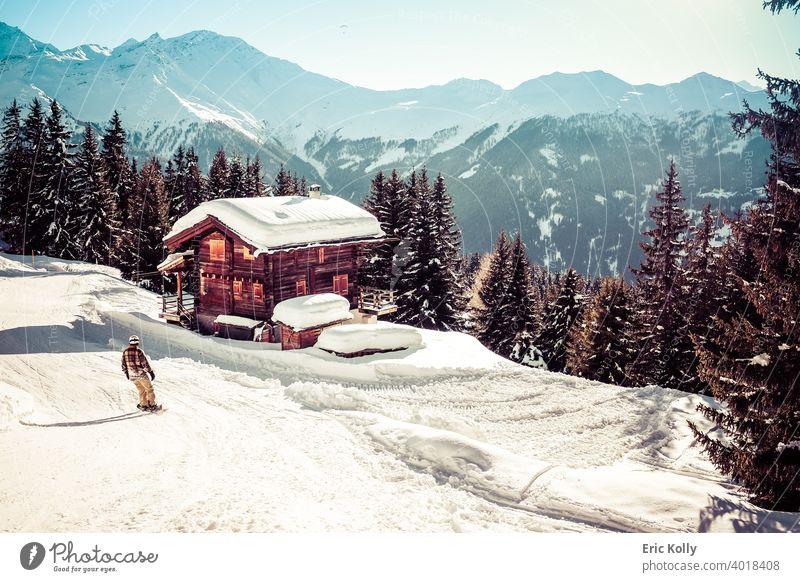 Skigebiet von Verbier mit einem Chalet mit Schnee bedeckt und ein Snowboarder im Vordergrund, aufgenommen in Verbier, Schweiz Winter kalt Außenaufnahme weiß