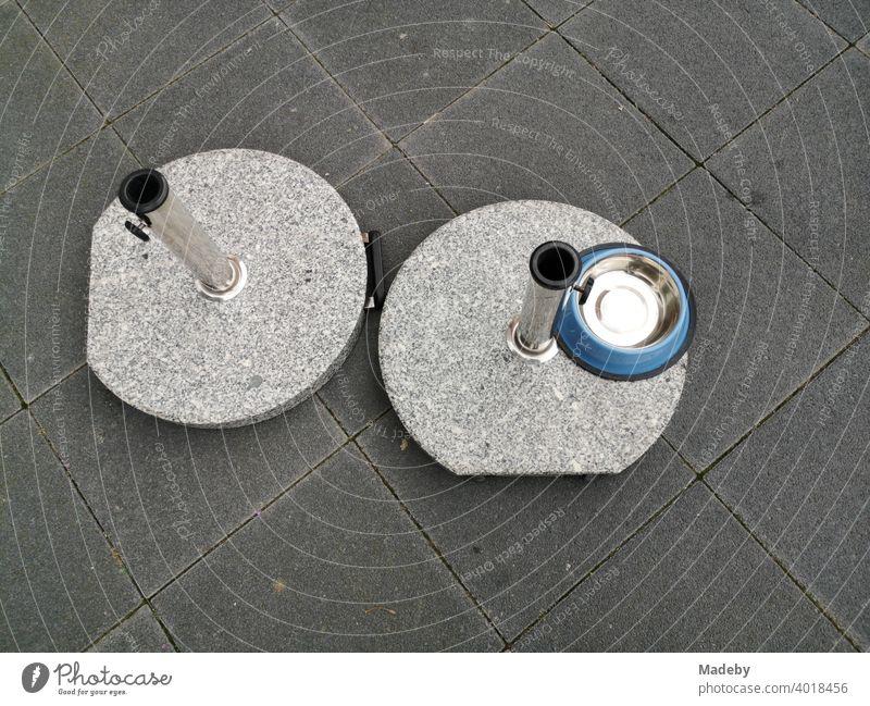 Runde Marmorständer für Sonnenschirme und runder Napf für Hunde auf grauem Straßenpflaster an der Hanauer Landstraße im Ostend von Frankfurt am Main