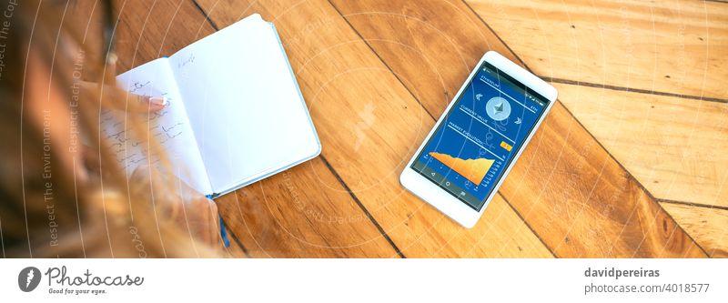 Geschäftsfrau macht sich Notizen in der Agenda und mobile Ethereum Informationen unkenntlich mitschreibend Kryptowährung Mobile Bildschirm arbeiten Transparente