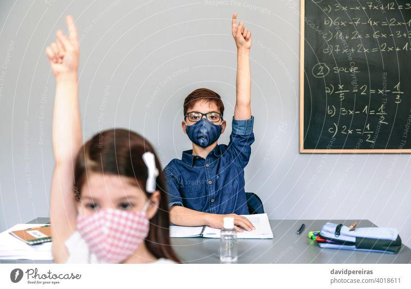 Schüler mit Masken heben die Hände in der Schule neue Normale Coronavirus Handreichung teilnehmend Gesichtsmaske Sicherheit Virus Menschen Mädchen Junge Seuche